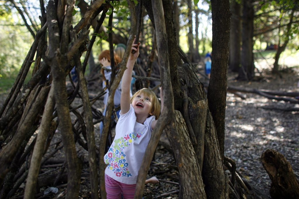 RENEE JONES SCHNEIDER ¥ reneejones@startribune.com Castle Rock, Minn. - 10/1/10 & 10/5/10 - GENERAL INFO - Building forts is a tradition in all childhoods, but at one small school, the art has been taken to a whole new level.  For more than 25 years, the woods surrounding Prairie Creek Community School near Northfield becomes a bustling village in the fall. Children race towards the small wooded area along the creek at the beginning of recess each day.  I myself was one of the first generations to buy sticks using the currency of corncobs to build my wooded dream house. ÒSticks for sale, two corn cobs,Ó chanted a group of girls as they walked past the former Òperfume shopÓ that now had become the woodsÕ Òcommunity center.Ó The main rules: everyoneÕs included and no running with sticks.   - IN THIS PHOTO ] Jillian Ros reached to located the perfect spot for her stick as her worked on fort during recess at Prairie Creek Community School recently. Ros had joined a fort made by fifth-graders who were happy to have little kindergartener join them.  For more than 25 years, the woods surrounding Prairie Creek Community School near Northfield becomes a bustling village in the fall. Children race towards the small wooded area along the Prairie Creek at the beginning of recess each day buying and selling sticks for their forts using corncobs.